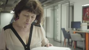 Mulher adulta que estuda papéis ao sentar-se em um escritório no local de trabalho Homem farpado que monta uma bicicleta nos loca video estoque