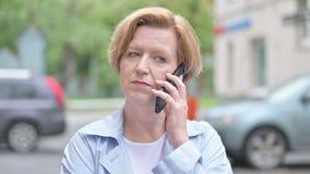 Mulher adulta que fala em Smartphone que está exterior video estoque
