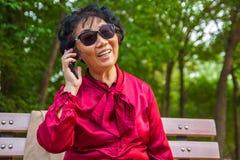 Mulher adulta que fala em um telefone celular e que smilling fotografia de stock