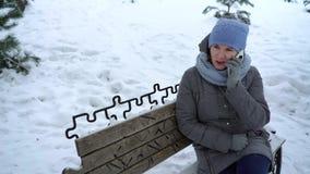 Mulher adulta que fala no telefone no parque do inverno vídeos de arquivo