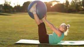 Mulher adulta que faz o exercício com fitball no parque vídeos de arquivo