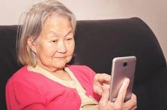 Mulher adulta que guarda um smartphone e que toca na tela imagens de stock