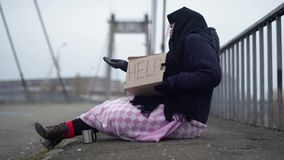 Mulher adulta que implora na rua Mendigo desabrigado que pede a ajuda filme