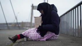 Mulher adulta que implora na rua Mendigo desabrigado que pede a ajuda Mulher adulta do proscrito video estoque
