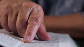 Mulher adulta que lê o livro grosso em casa Avó com a Bíblia Pensionista idoso concentrado com os enrugamentos nas mãos video estoque