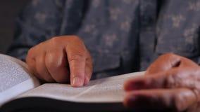 Mulher adulta que lê o livro grosso em casa Avó com a Bíblia Pensionista idoso concentrado com os enrugamentos nas mãos vídeos de arquivo