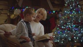Mulher adulta que lê um livro para um rapaz pequeno e que fala a ele na noite de Natal vídeos de arquivo