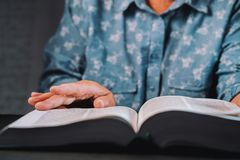Mulher adulta que lança através das páginas do livro Avó com a Bíblia Pensionista idoso concentrado com os enrugamentos nas mãos imagem de stock