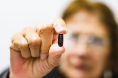 Mulher adulta que mostra um comprimido no primeiro plano, conceito da saúde dos sêniores foto de stock