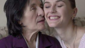 Mulher adulta que olha em uma janela Menina que vem, abraçando e sorrindo lentamente vídeos de arquivo