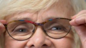 Mulher adulta que põe monóculos sobre o close up, verificação da visão, saúde da oftalmologia filme