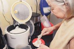 Mulher adulta que põe o arroz branco sobre uma bacia fotografia de stock