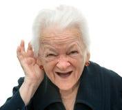 Mulher adulta que põe a mão a sua orelha. Audição má Fotografia de Stock Royalty Free