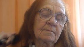 Mulher adulta que penteia seu cabelo em casa filme