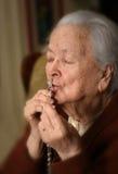 Mulher adulta que reza e que guarda o rosário de prata fotos de stock royalty free