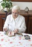 Mulher adulta que senta-se na sala de visitas na tabela e em olhares em fotografias velhas Imagem de Stock