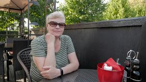 Mulher adulta que senta-se na tabela da varanda exterior no restaurante vídeos de arquivo