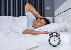 A mulher adulta que sofre da insônia está tentando dormir na cama imagem de stock
