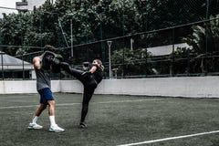 Mulher adulta que treina tailandês de Muay com treinador masculino Fotografia de Stock Royalty Free