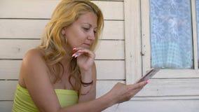 Mulher adulta que usa o telefone celular no terraço exterior na casa de verão vídeos de arquivo