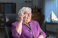 Mulher adulta que usa um telefone celular fotografia de stock