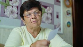 Mulher adulta superior Defocused nos monóculos que verifica custos de despesas diárias em casa vídeos de arquivo