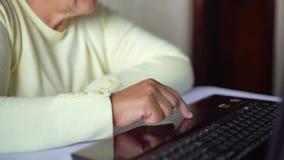 Mulher adulta superior nos monóculos que surfam o Internet no close up do portátil em casa video estoque