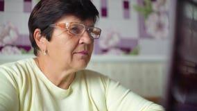 Mulher adulta superior nos monóculos que surfam o Internet no close up do portátil em casa com espaço livre e da cópia vídeos de arquivo