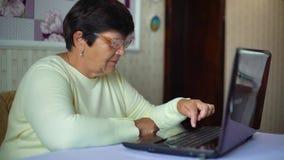 Mulher adulta superior nos monóculos que surfam o Internet no portátil em casa video estoque