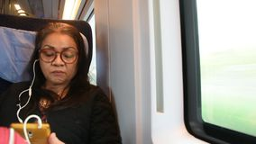 A mulher adulta tailandesa asiática que joga o telefone do moblie e escuta música quando se sente no trem vídeos de arquivo