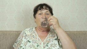 A mulher adulta toma o comprimido, bebe a água do vidro filme
