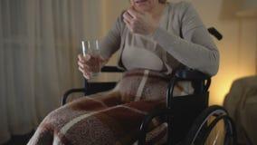 Mulher adulta triste na cadeira de rodas que toma a medicina, período da recuperação, depressão filme