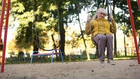 A mulher adulta triste só que monta no balanço no parque, nos nenhuns amigos e na família, abandonou fotografia de stock
