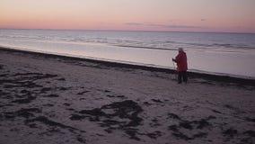 A mulher adulta vai com as bengalas nórdicas ao longo do litoral video estoque