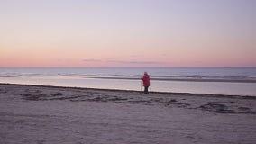 A mulher adulta vai com as bengalas nórdicas ao longo do litoral vídeos de arquivo