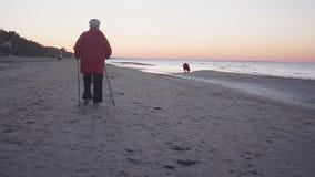 A mulher adulta vai com as bengalas nórdicas ao longo do litoral filme