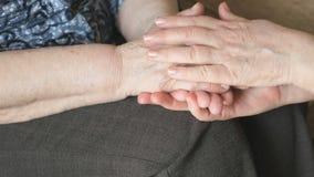 A mulher afaga a mão de uma mulher enrugada idosa vídeos de arquivo