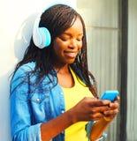 A mulher africana bonita com fones de ouvido escuta a música usando o smartphone fotos de stock royalty free