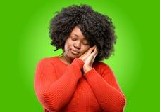 Mulher africana bonita com o cabelo encaracolado isolado sobre o fundo verde fotografia de stock