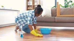 Mulher africana com o assoalho da limpeza da esponja em casa filme