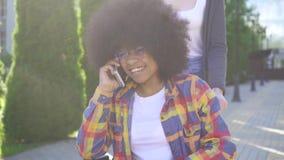 A mulher africana com um penteado afro desabilitou em um positivo da cadeira de rodas que fala no telefone no parque video estoque