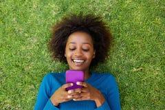 Mulher africana de sorriso que encontra-se na grama que olha o telefone celular Fotografia de Stock Royalty Free