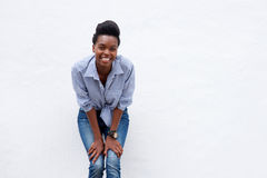 Mulher africana de sorriso que inclina-se contra a parede branca Fotografia de Stock