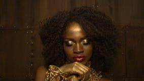 Mulher africana encantador com os bordos lustrosos vermelhos grandes, sombras douradas e o cabelo encaracolado escuro vestindo a  filme