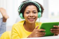 Mulher africana feliz com PC e fones de ouvido da tabuleta imagens de stock