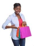 Mulher africana feliz que apresenta seus sacos de compras Fotos de Stock Royalty Free