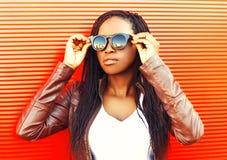 Mulher africana nova à moda que veste um revestimento, óculos de sol na cidade imagens de stock