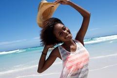 Mulher africana nova alegre na praia imagem de stock