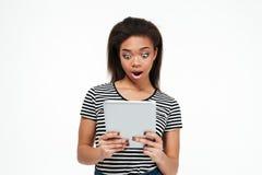 Mulher africana nova chocada que usa o tablet pc Imagens de Stock Royalty Free