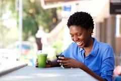 Mulher africana nova feliz que senta-se no café exterior usando o telefone celular imagem de stock